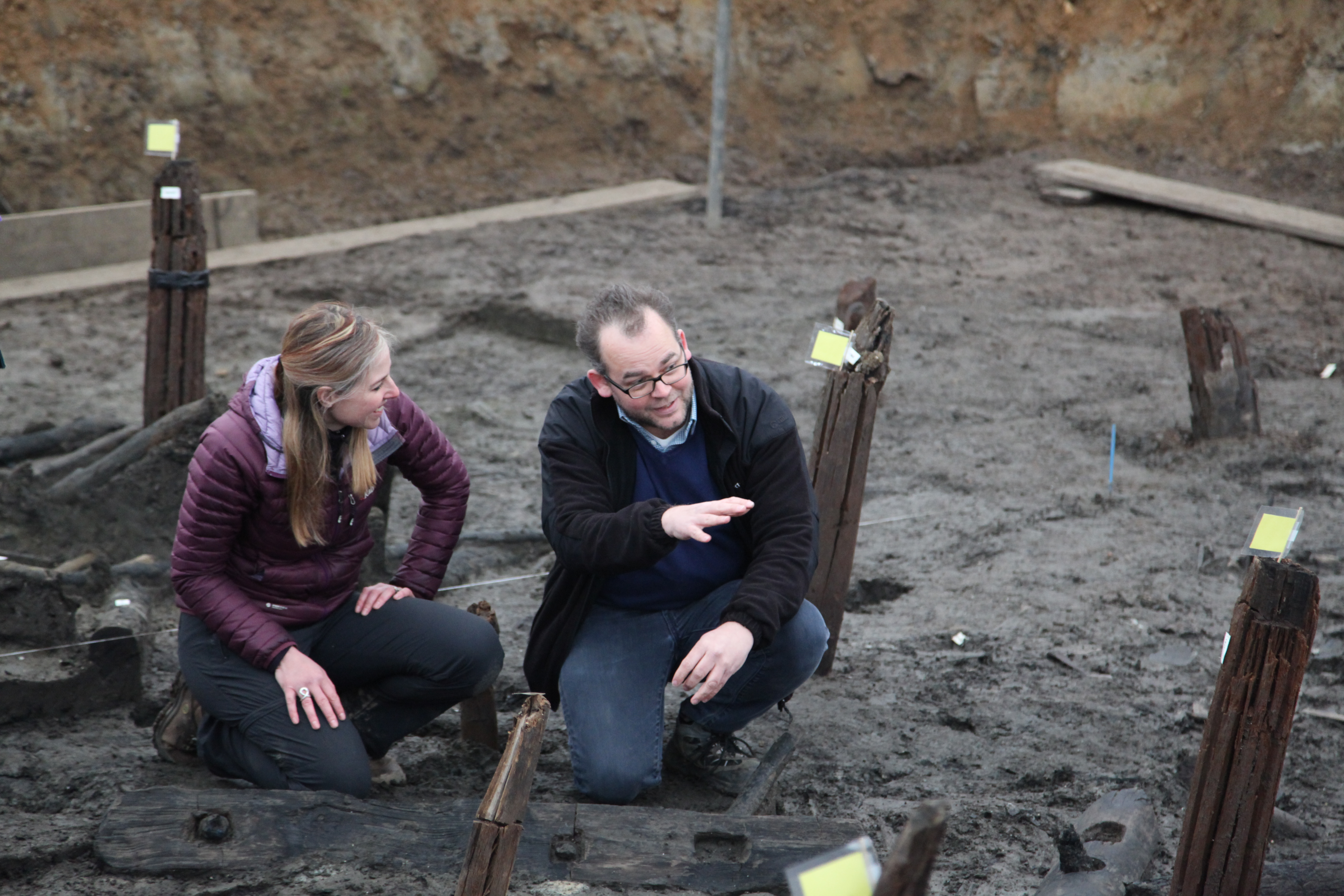 Alice Roberts kneeling and talking to Dr. Karl Harrison, forensic archeologist, Cranfield University, in a trench (Lake Constance).