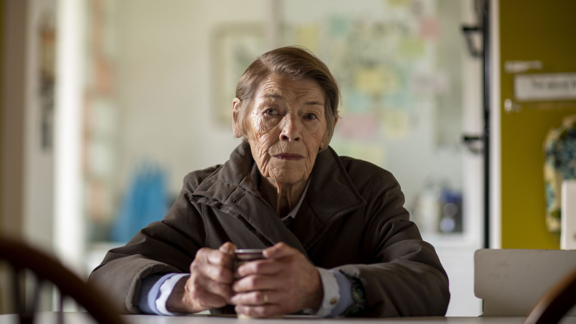 An elderly woman with short grey hair sits in a brown overcoat at a kitchen table, her hands around a mug of tea. She stares thoughtfully in the distance. Behind her is a blurred view of a wall with multicolor post-it notes.