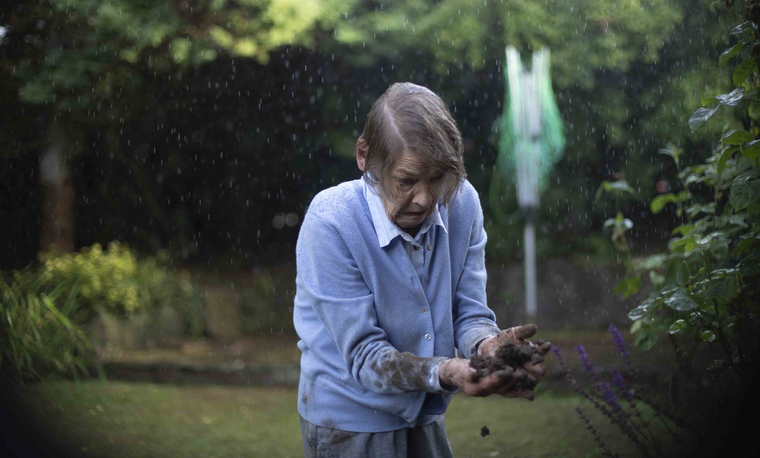An elderly woman in a blue sweater and shirt stands in the rain in a garden looking with fear at her hands, which are full of dirt. The arms of her sweater and her pants are stained with dirt.