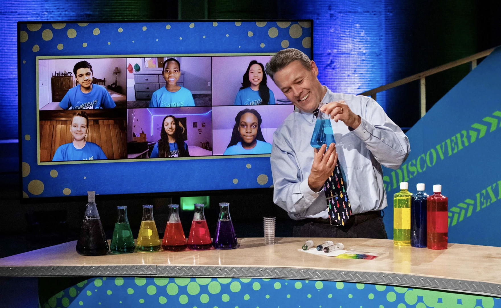 A smiling male teacher in a shirt and tie holds a beaker filled with blue water. He stands behind a long desk with five other beakers with blue, green yellow, red, and purple water, and some bottles of food coloring. Behind him is a screen with a Zoom image of six students, a boy and five girls, wearing matching blue shirts.