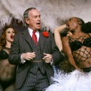 "In this April 3, 2004 file photo, New York City Mayor Michael Bloomberg performs a comedy routine with the cast of the Broadway musical ""Chicago"" during the Inner Circle dinner in New York. New Yorkers are fascinated by the mayor's fortune and the lifestyle that comes with it. His wealth has helped raise Bloomberg's national profile, fed speculation that he would make a self-funded run for the presidency, and provided evidence to voters of the business acumen that was a major rationale for his candidacies. (AP Photo/John Marshall Mantel, File)"