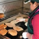 "A woman cooks up fresh tortillas out of a truck on Roosevelt Ave. in Jackson Heights, Queens. Many immigrant food vendors, particularly women, face stiff fines and even confiscation of their equipment, since they often can't afford to buy permits off what tour guide Andrew Silverstein calls the ""grey market."" Photo courtesy of Streetwise New York."