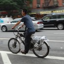 A man rides an electric bicycle down Ninth Avenue in Hell's Kitchen. MetroFocus/ Georgia Kral