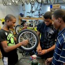 Teens working on a wheel in the Recycle a Bicycle shop. Photo courtesy of Recycle a Bicycle
