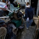 a friend helps clean up a home belonging to Eileen Mannix in the Midland Beach neighborhood in the hard hit Staten Island borough New York, Sunday, Nov. 4, 2012, in the wake of Hurricane Sandy. AP Photo/Craig Ruttle.