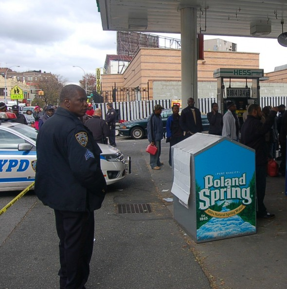 An NYPD officer monitors the line at a gas station in Flatbush, Brooklyn, on Nov. 1, 2012.