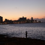 The Havana skyline. A fisherman takes a break from the bustle of the city.