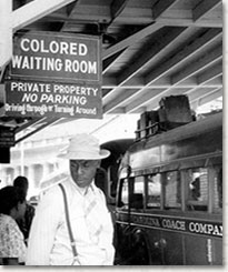 Photo of an African American man standing below a sign for a segregated waiting room at