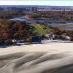 In Pelham Bay Park in the Bronx, what was once a crowded mass of summer cottages on the shore of Long Island Sound was converted into a vast sandy public beach when the water between Rodman's Neck and Hunter Island was filled to create Orchard Beach's wide crescent. Photo courtesy of NYC Media.